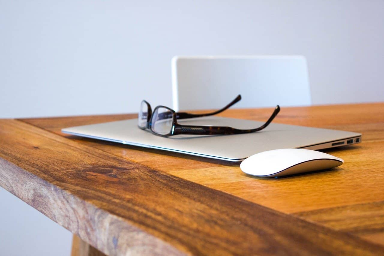 A set of glasses lay on top of a silver laptop on a wood table.
