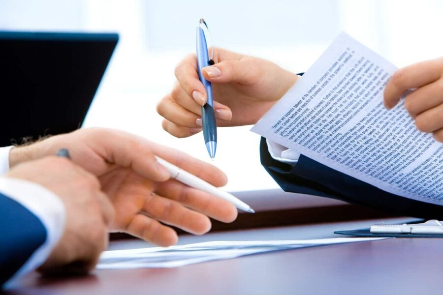 Two accountants meet and go over a contract placed on a desk.